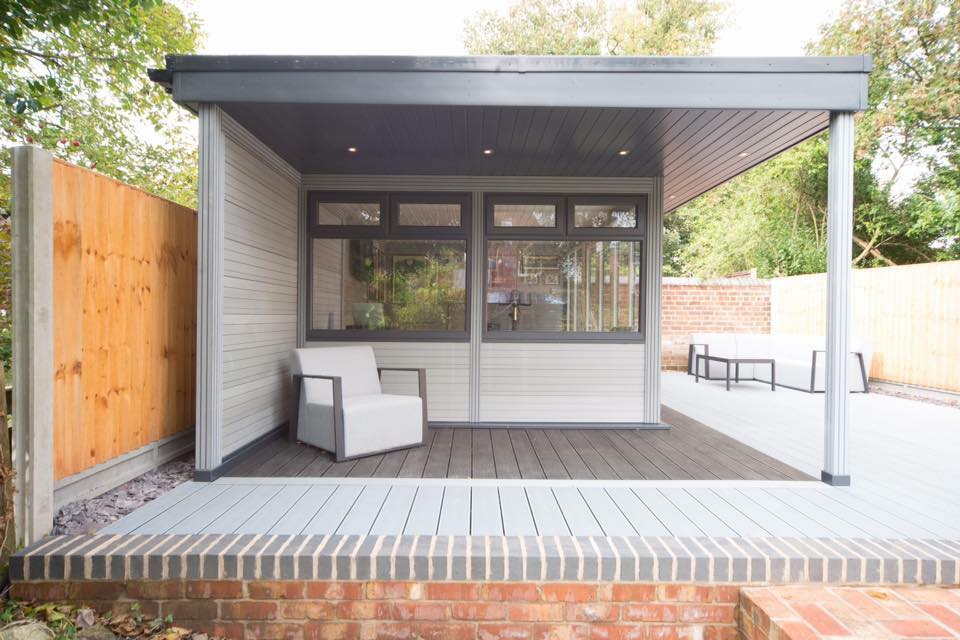 A grey garden room, complete with decking and outdoor seating