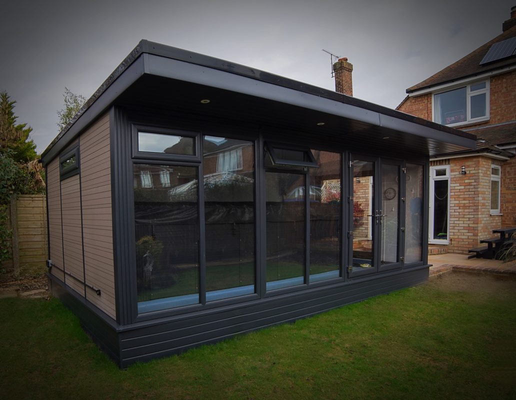 A garden room, outside a domestic property with large glass front and bi-fold door